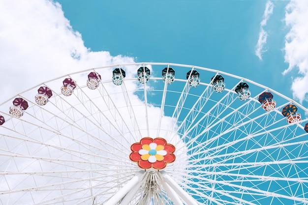 Una ruota panoramica di colore bianco con cabine colorate contro il cielo blu.