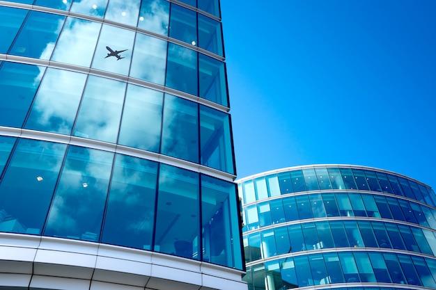 Una sagoma di aeroplano jet con ufficio d'affari torri sfondo, londra