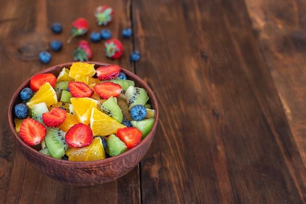 Una sana insalata di frutta fresca in ciotola sulla tavola di legno scuro. con copia spazio