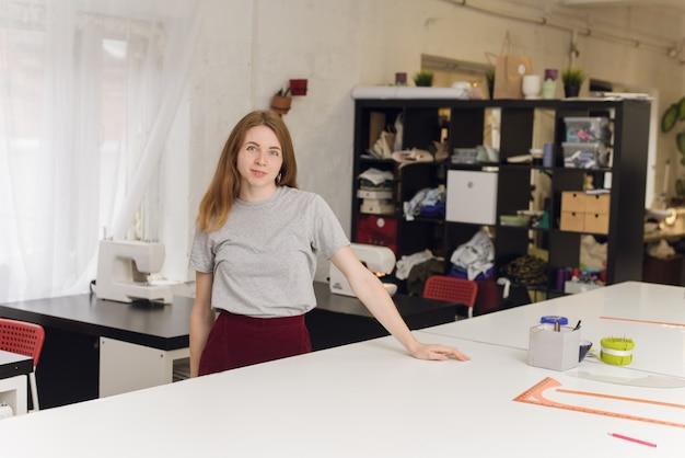 Una sarta felice in una posa dello studio di cucito. ritratto di una bella sarta che trasporta un metro a nastro e lavora in una fabbrica tessile