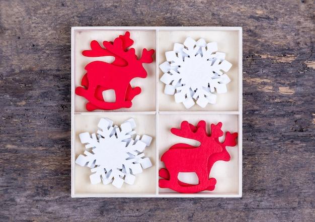 Una scatola bianca con scomparti su uno sfondo di legno riempito con giocattoli di cervi di natale rosso e fiocchi di neve bianchi