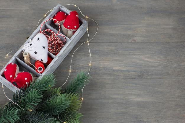 Una scatola con decorazioni natalizie fatte a mano, fili, aghi, un ramo di abete e ghirlanda