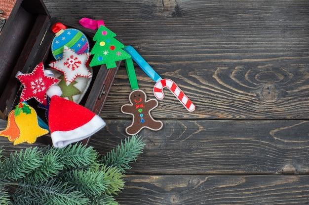 Una scatola con decorazioni natalizie fatte a mano in feltro e tessuto, un ramo di abete rosso e una ghirlanda