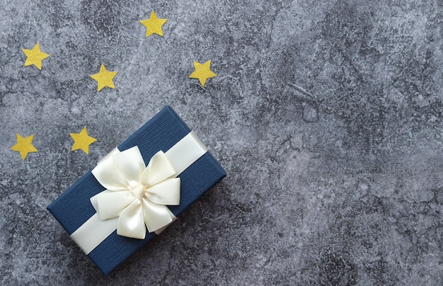 Una scatola con un regalo per un uomo, una superficie di cemento grigio