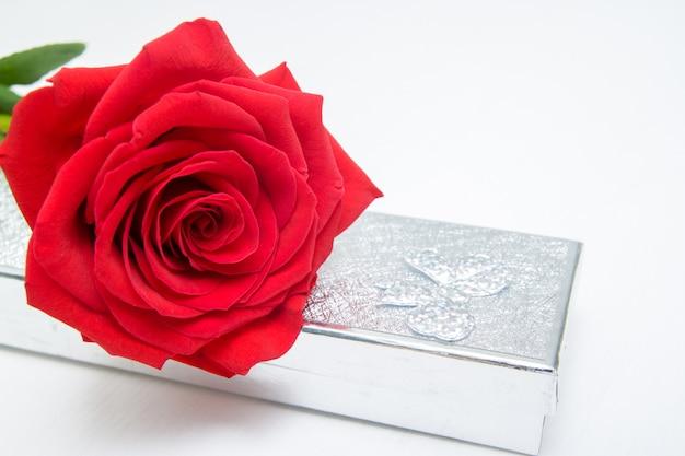 Una scatola del presente dei gioielli e della rosa rossa su fondo di legno bianco