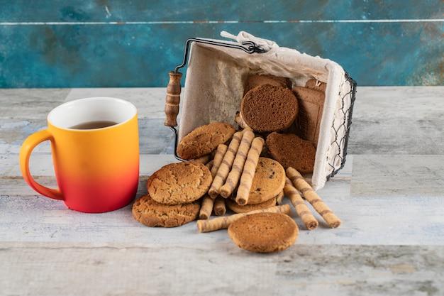 Una scatola di biscotti con una tazza di tè