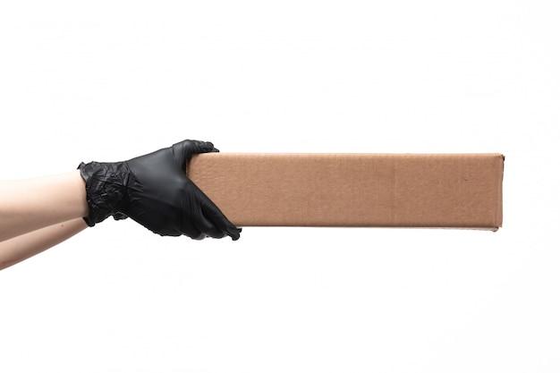 Una scatola di consegna femminile della tenuta della mano di vista frontale sul lavoro bianco