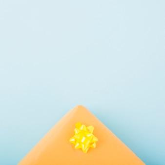 Una scatola regalo con fiocco di nastro di raso giallo su sfondo blu