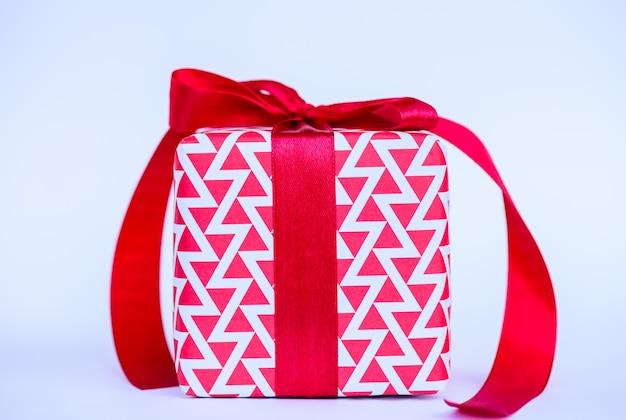 Una scatola regalo con nastro rosso su sfondo bianco ..