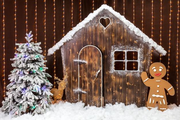 Una scena di natale con una capanna coperta di neve, un omino di pan di zenzero e un albero di natale. decorazione della foresta da favola.