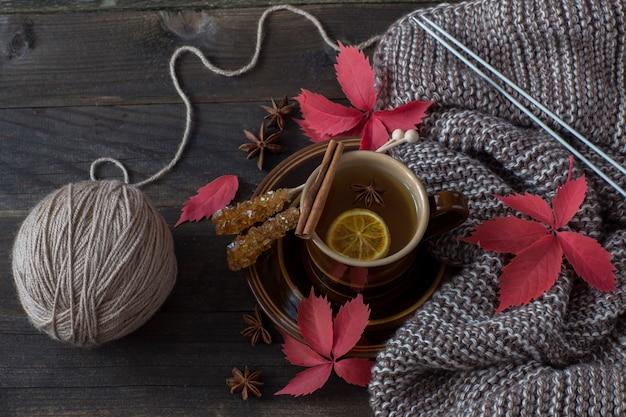 Una sciarpa, foglie d'autunno, fette di limone, zucchero, cannella, una tazza di tè al limone, ferri da calza