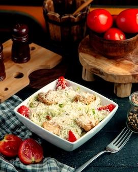 Una scodella di pollo caesar salad con formaggio extra grattugiato