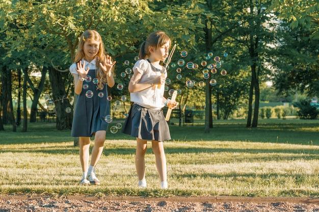 Una scolara di due amiche gioca con le bolle di sapone