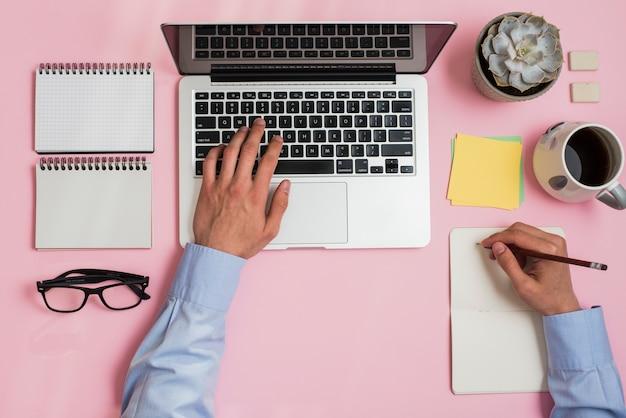 Una scrittura della persona di affari sul blocchetto per appunti che digita sul computer portatile sopra la scrivania