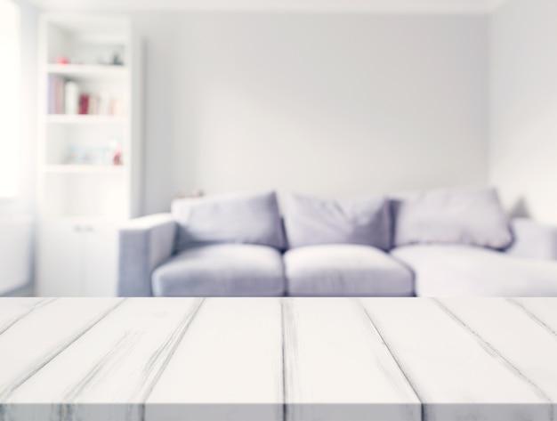 Una scrivania bianca vuota davanti al divano sfocato nel soggiorno