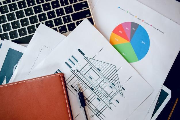 Una scrivania con un notebook aziendale, un grafico e un tavolo. vista dall'alto con lo spazio della copia