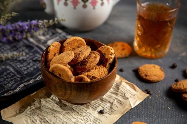 Una scrivania con vista frontale con bollitore per il tè e biscotti con superficie grigia, biscotto per il tè, dolce