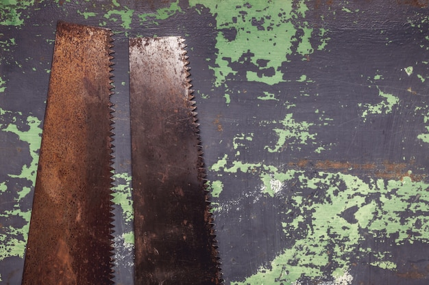 Una sega di due mani dell'annata sulla vecchia superficie di metallo