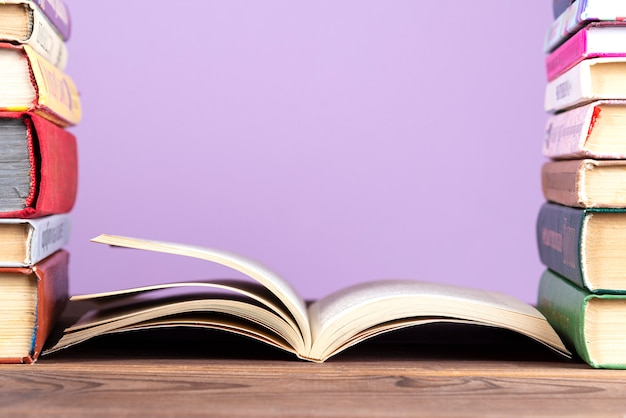 Una semplice composizione di molti libri con copertina rigida, libri multicolori su un tavolo di legno e uno sfondo di colore lilla.
