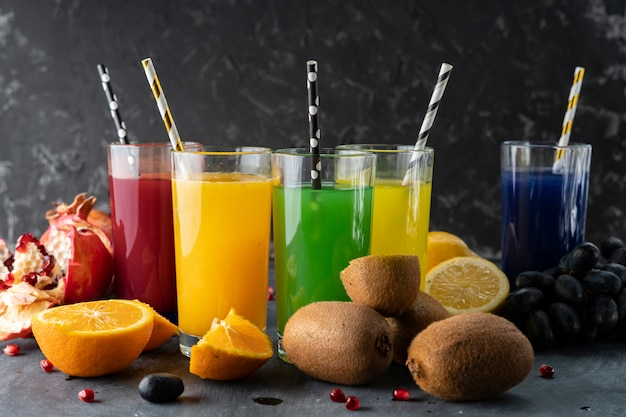 Una serie di freschi spremute fresche o cocktail in bicchieri fatti di arancia, kiwi, limone, uva, melograni