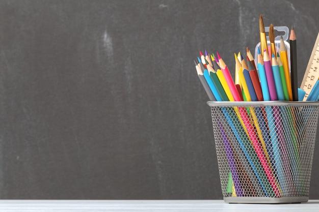 Una serie di matite, pennelli, vernici sullo sfondo del consiglio scolastico.