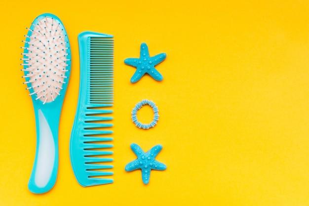Una serie di pettini, una fascia per capelli e un fermaglio per capelli su una vista superiore gialla