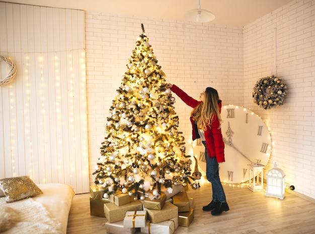 Una signora che decora l'albero di natale, con uno stile bianco dorato