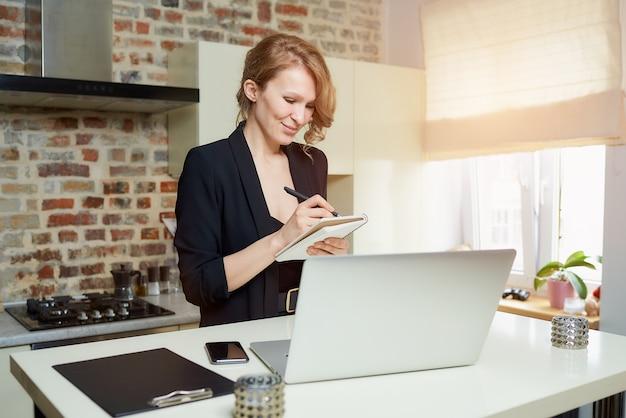 Una signora lavora a distanza su un laptop in cucina. una ragazza felice che fa appunti sul quaderno durante il rapporto di un collega durante una videoconferenza a casa.