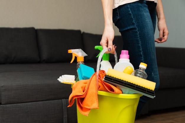 Una signora tiene in mano un secchio di prodotti e attrezzature per la pulizia