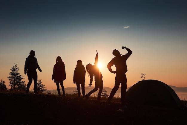 Una silhouette di persone di gruppo si diverte in cima alla montagna vicino alla tenda durante il tramonto.