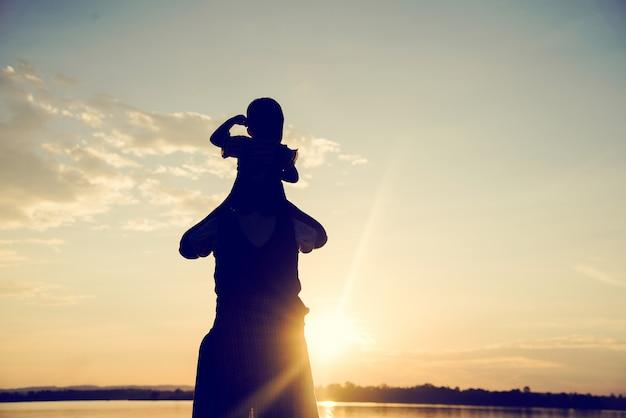 Una siluetta di una famiglia armoniosa felice della giovane madre all'aperto.
