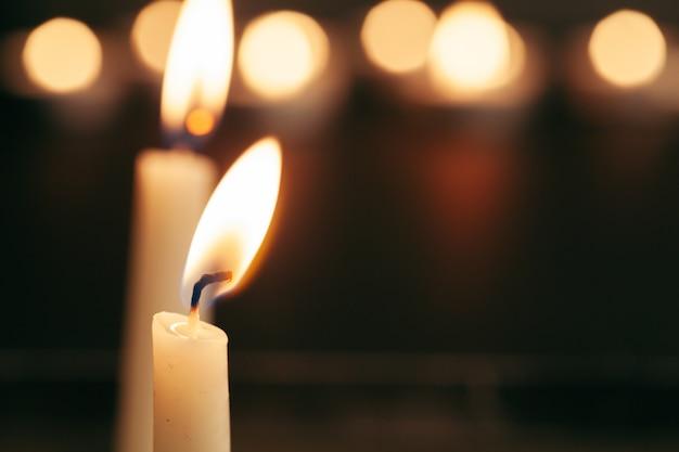 Una singola candela accesa isolata con il nero