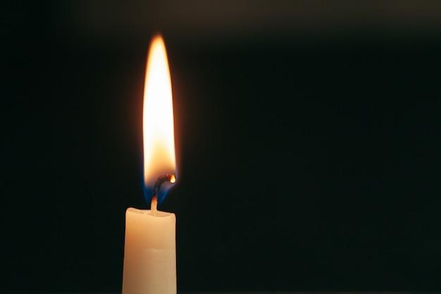 Una singola candela accesa isolata con sfondo nero