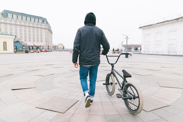 Una spina dorsale di un giovane che cammina per la città con una bici bmx. cammina con una bici.