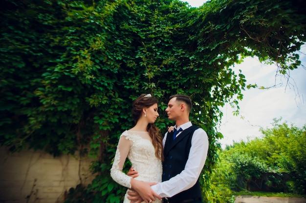 Una sposa con un taglio di capelli corto e uno sposo elegante cammina nel parco.