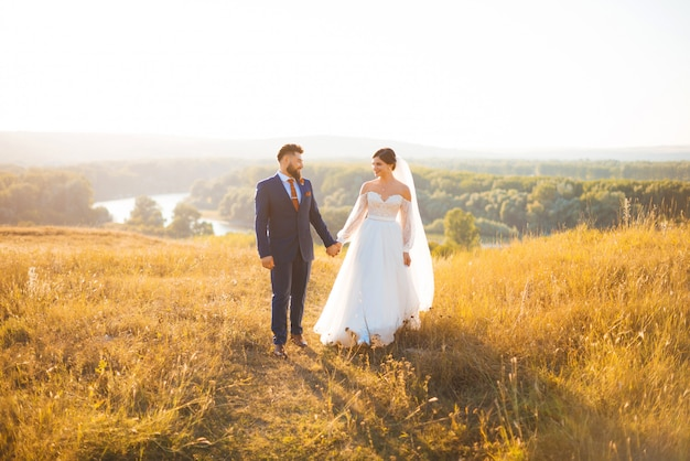 Una sposa e uno sposo sta camminando su un campo al tramonto, alla luce del sole, tenendosi per mano.