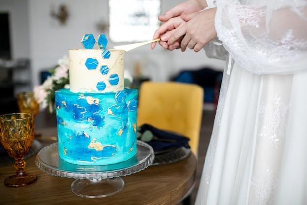 Una sposa e uno sposo stanno tagliando la loro torta nuziale