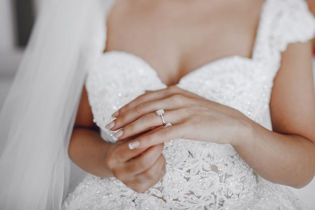 Una sposa elegante e bella a casa in piedi vicino alla finestra