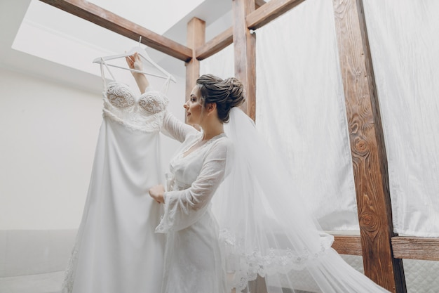 Una sposa giovane e bella a casa sta per un matrimonio