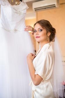 Una sposa in vestaglia viene al suo abito da sposa