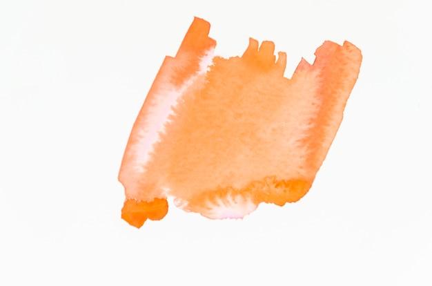 Una spruzzata arancio arancione astratta dell'acquerello isolata sul contesto bianco