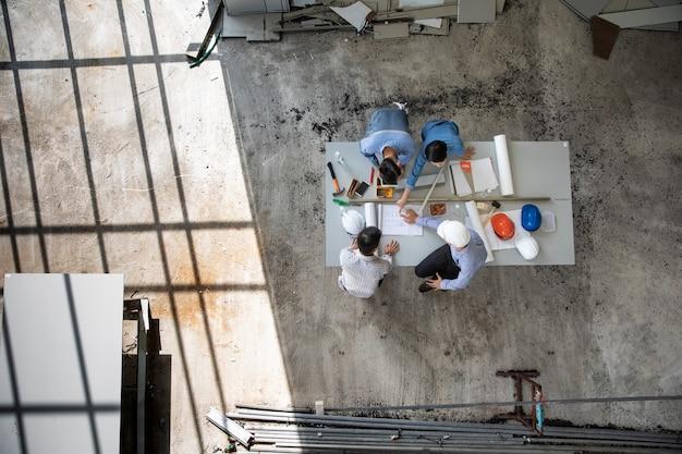 Una squadra di ingegneri di quattro persone parla insieme per rivedere il materiale da costruzione e il brainstorming