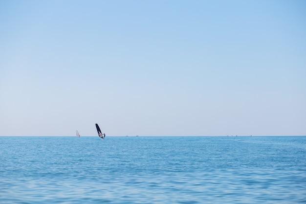 Una squadra di surfisti galleggia sul mare facendo windsurf