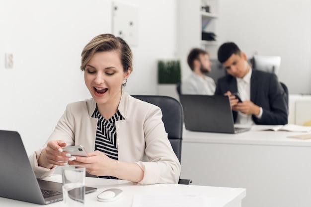 Una stagista in un'agenzia immobiliare è felice della sua prima transazione online con un cliente. in possesso di uno smartphone.