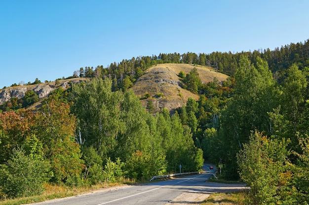 Una strada asfaltata nella foresta e nelle montagne.