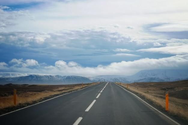 Una strada in un campo con un bel cielo nuvoloso