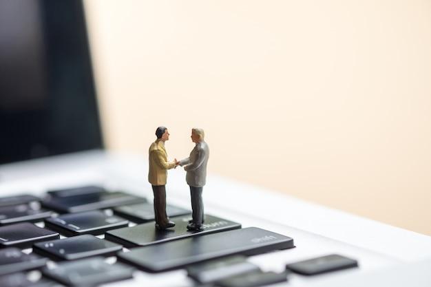Una stretta di mano di due figure miniatura dell'uomo d'affari sul computer portatile.
