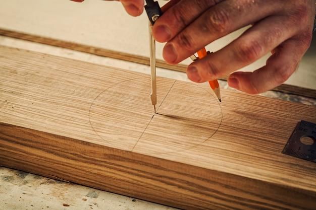 Una stretta di un maschio carpentiere segna matita