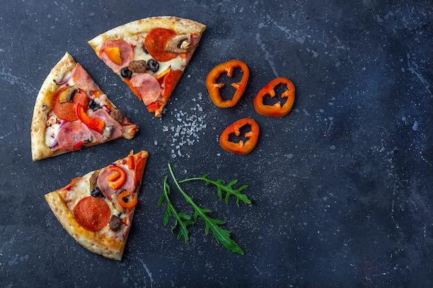 Una striscia di pizza fresca preparata con salame, funghi, prosciutto e formaggio su uno sfondo scuro. pranzo o cena tradizionali italiani. concetto di fast food e cibo di strada. disteso,