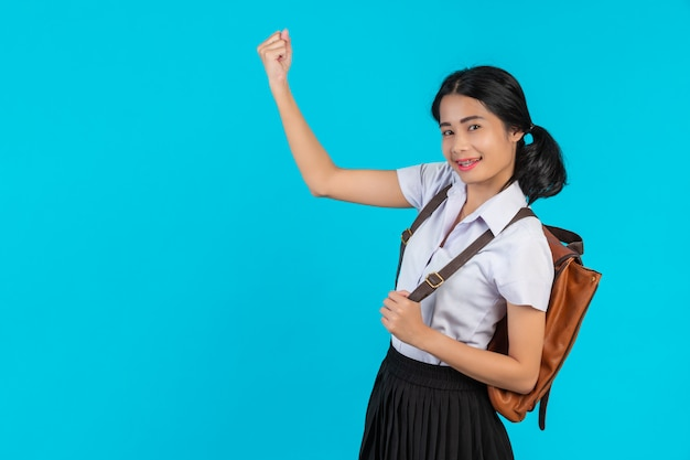 Una studentessa asiatica spia la sua borsa di cuoio marrone su un blu.